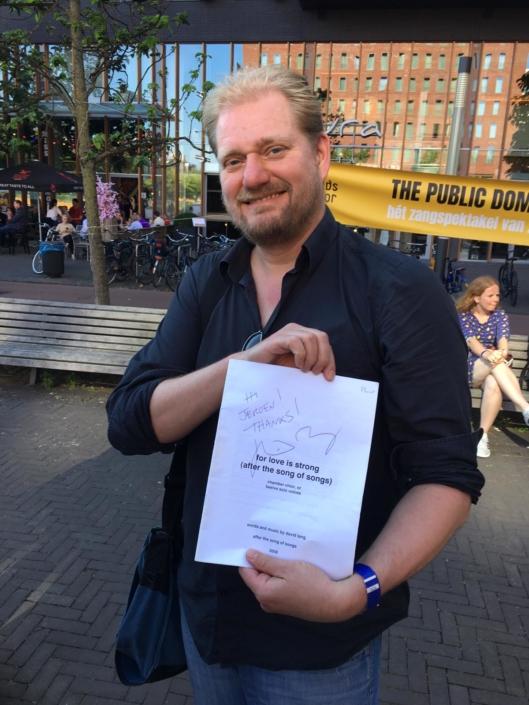 Foto van Jeroen Spitteler die handtekening laat zien op bladmuziek For Love Is Strong